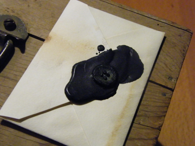 On top of the box was a letter, sealed with black wax and a black button.